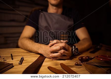 Working process of the leather belt in the leather workshop. Man holding hands on wooden table. Crafting tools on background. Tanner in old tannery. Close up men arm. Interlock fingers.