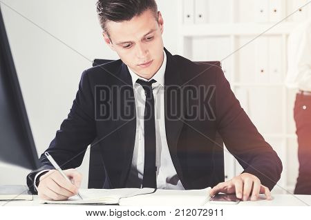 Serious young manager with fair hair wearing a suit is working with papers in his office. Concept of a business lifestyle. Toned image