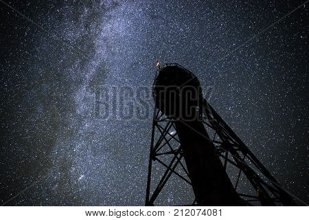 Silhouette Of The Old Lighthouse Against The Background Of The Starry Sky