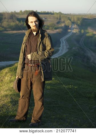 A young man stands on a grass hill in a sunny spring evening. A field and a road are in the background. The man has lond dark hair and a beard, dressed in brown and holds a cap in his hand.