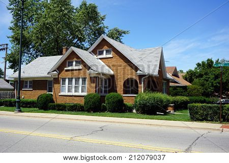 A brown brick single family home on Ruby Street in Joliet, Illinois, during July.