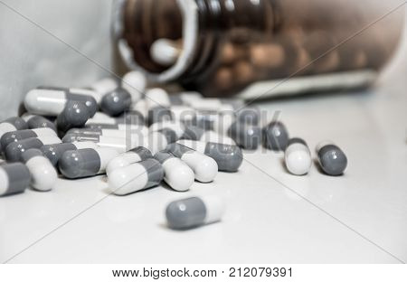 Open Pill Bottle with Capsules spilled all over Counter close up on the Top of the bottle and pills into the pill bottle black and white