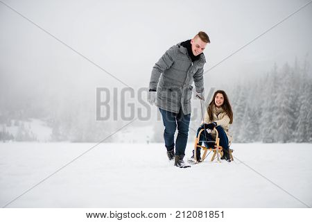 Smiling man dragging woman on sledge in winter