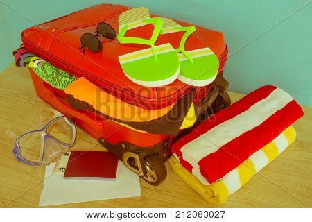 Anticipation of voyage. Women's clothes and accessories in red suitcase things prepared for travel - Retro color