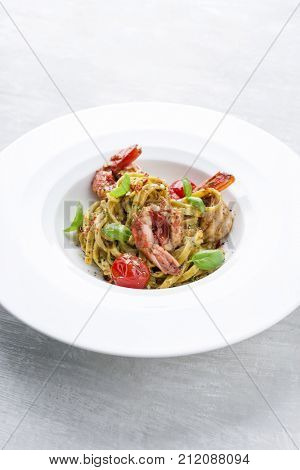 Traditional Italian tagliatelle ai gamberoni with tomatoes as close-up on a plate