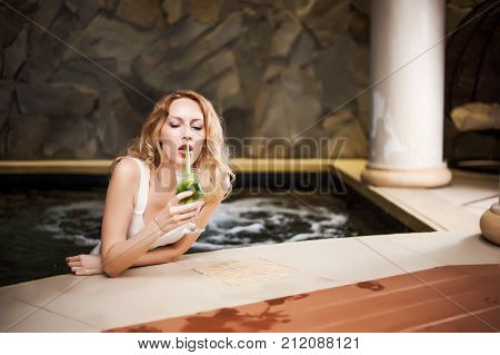 Model Girl With Blond Hair In Jacuzzi Drinks Green Mojito
