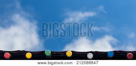 Happy holiday event celebration background concept: line of colorful light bulbs on the roof eaves looking up blue sky and white clouds in background