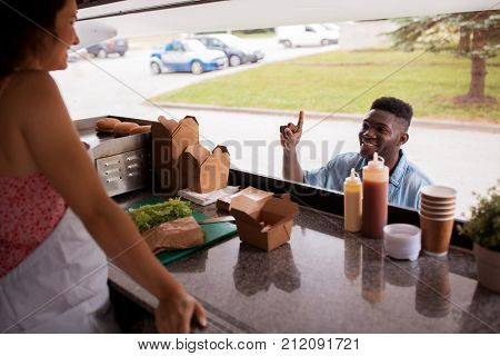 street sale and people concept - happy african american young man ordering wok at food truck