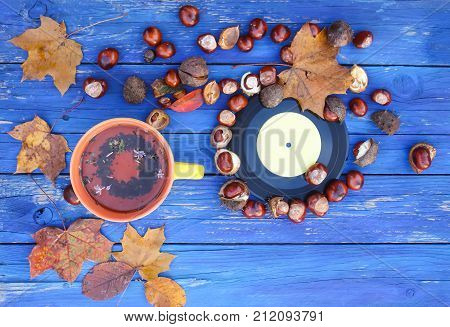 Yellow ceramic cup of herbal tea and vintage vinyl records on aged wooden background with fall autumn leaves and chestnuts.