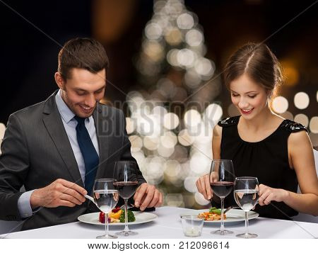people and holidays concept - smiling couple eating main course at restaurant over christmas tree background