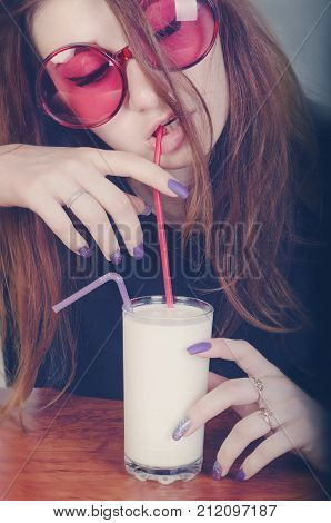 a girl in pink glasses drinks milk through a straw