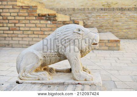 Ancient stone lion sculpture against brick wall Bukhara Uzbekistan