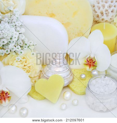 Beauty treatment cleansing and exfoliation products with orchid and carnation flowers, exfoliating salt, heart shaped soap, sponges, with seashells and decorative pearls on white wood background.