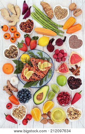Health food for a healthy heart with salmon, vegetables, fruit, nuts, seeds, spices and herbs used in herbal medicine. Super food concept, high in omega 3, anthocyanins, antioxidants and vitamins.