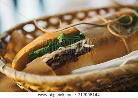 Close-up sandwich with meat, cucumber and greens wrapped in paper and fastened with rope lies in basket on the table.
