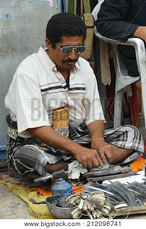 SANAA, YEMEN - SEPTEMBER 18, 2006: Unidentified man sharpens janbiya in Sanaa, Yemen. Janbiya is a traditional dagger and a mandatory attribute of Yemeni men's suit.