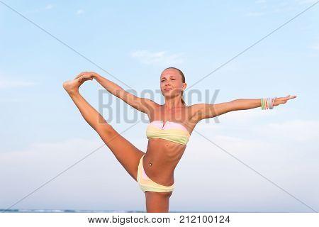 Woman doing yoga asana at the beach
