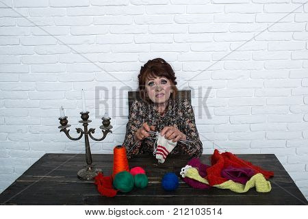 Old Woman Knitting Socks From Colorful Thread.
