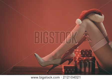 Christmas legs of woman in stocking and shoes. New year legs on red background with present. Santa claus gift box and hat copy space. Xmas party holiday celebration. Boxing day and christmas sale.