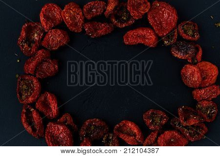 Sun dried dried tomatoes close up on a black background copy space
