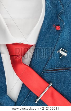 Men's fashion. Elegant denim jacket with a red tie. Male jacket with tie and cufflinks tie clip close-up