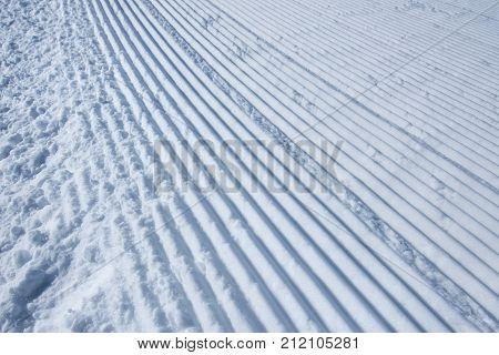 Groomed ski run track in snow winter season background