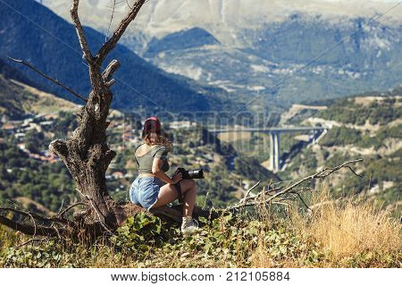 Young female photographer with professional camera near big old tree opposite greek village. A girl with camera opposite the village of Metsovo in Greece.