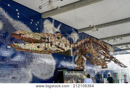 LISBON PORTUGAL - MAY 5 2008: The ticketing foyer of Lisbon Oceanarium with strange suspended creature made entirely of crushed aluminum cans in Lisbon on May 5 2008.