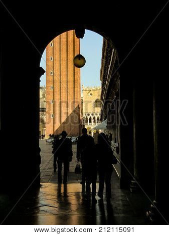 Arch or door in deep shadow behind Saint Mark square in Venice with tourists in shadow and shadow passing through.