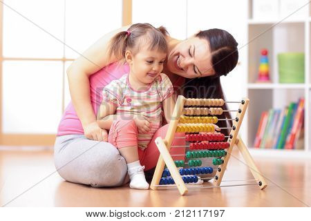 kid girl and mother playing with abacus at home interior