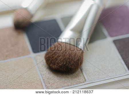 Make up eye shadows set and brushes closeup background. Shallow DOF