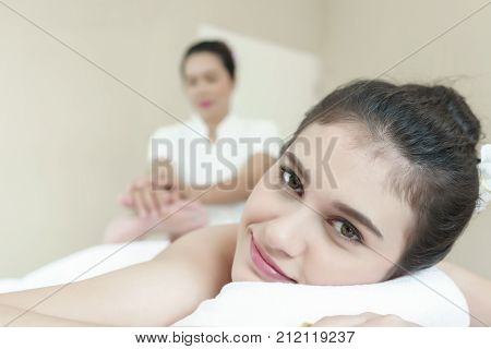 Beautiful young Asian woman relaxing lying on massage table and having Thai traditional massage in spa salon