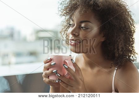 Outgoing young mulatto female tasting cup of appetizing coffee while looking at window at home. Copy space