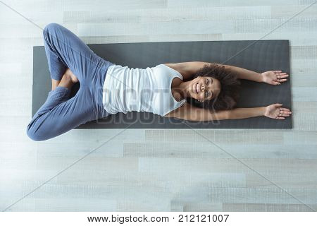 Top view cheerful mulatto girl locating on mat while doing exercise at home