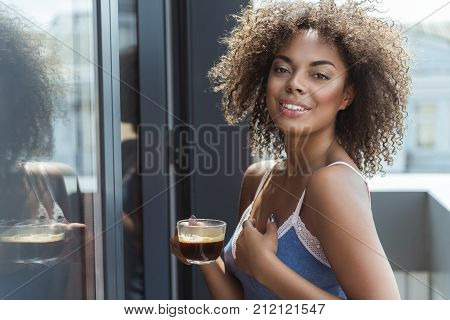 Portrait of beaming young mulatto girl drinking cup of delicious coffee in morning. She looking at camera