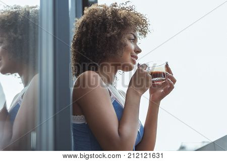 Side view low angle smiling mulatto girl tasting mug of appetizing beverage. Copy space