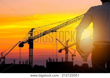 architect and engineer concept Silhouette of working man standing and holding safety helment and sheet of paper building structure with crane and building background in sunset