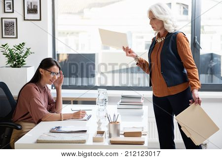 This is bad. Senior lady boss is standing near desk of her young assistant and holding folders while expressing discontent. Girl is sitting at table while frowning her forehead and feeling frustration
