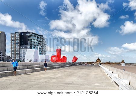 OSTENDE BELGIUM - JUNE 9 2017: The embankment in Ostende. Modern abstract conceptual sculptures of red color on the seashore in Ostende