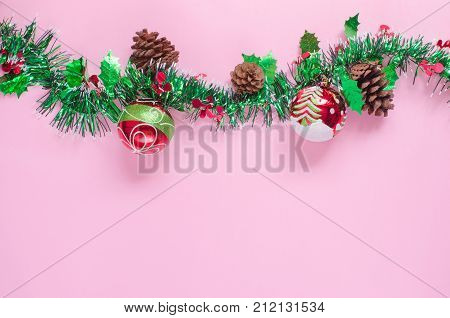 Christmas decorative red balls painted with white snow green pine tree and cone white curved circle lines & green big line on pink background and space with green white shiny decoration for xmas tree