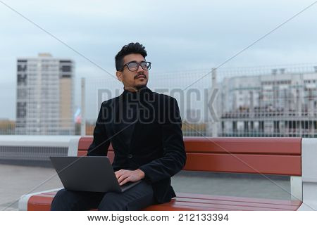 Young Businessman In Eyeglasses Work On The Laptop Sitting Outdoors.