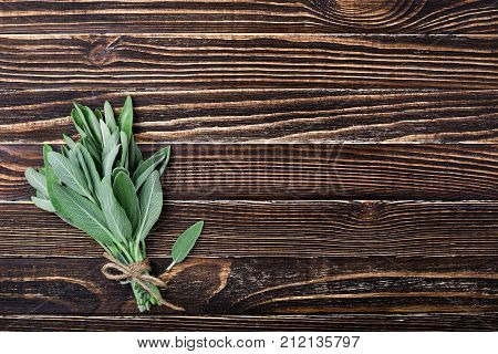 Fresh sage on old wooden background. Aromatic bunch of sage. Gardening herbs. Top view