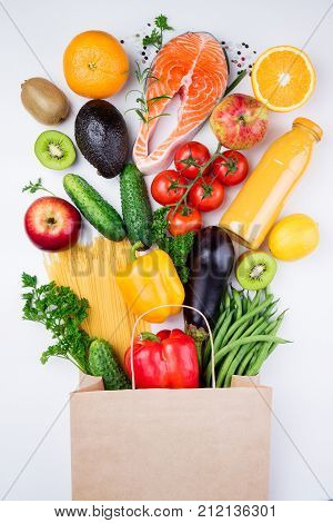 Healthy food background. Healthy food in full paper bag of different products fish vegetables and fruits on white background. Top view