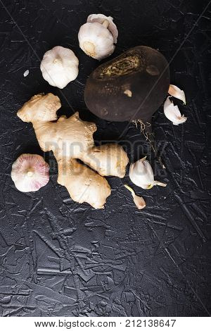 Tuber black radish and garlic on a black concrete background. Top view