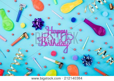 Happy birthday background. Festive candles party confetti balloons streamers and decoration on blue background. Colorful celebration background. Flat lay