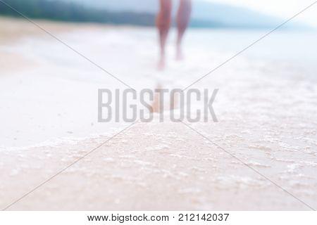 A Woman Walks Along The Beach