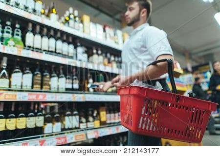 A man with a product basket looks at the supermarket shelf and chooses wine. A man makes purchases in the store. Focus on the basket