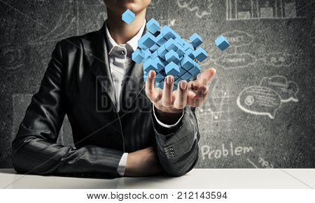 Cropped image of business woman in suit presenting multiple cubes in hand as symbol of innovations. Business sketches on background. 3D rendering.