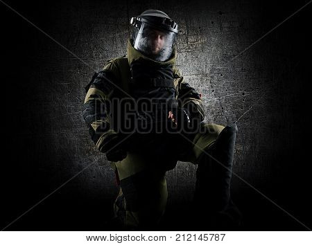 Military man in a protective sapper suit is kneeling and is preparing to neutralize the bomb. Mixed media