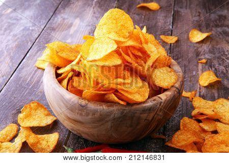 Crispy potato chips. Paprika chips on brown wooden background.